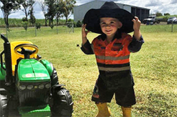 Child with hat next to tractor on peanut farm